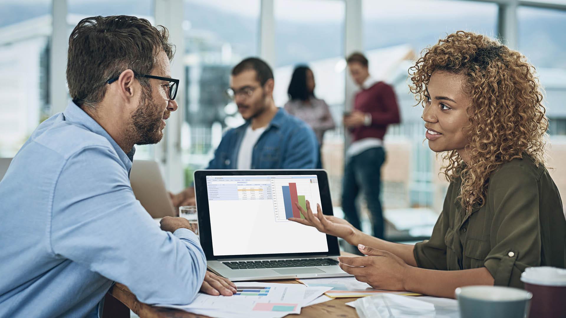 Vrouw legt man iets uit over Alure Practice Management op laptop
