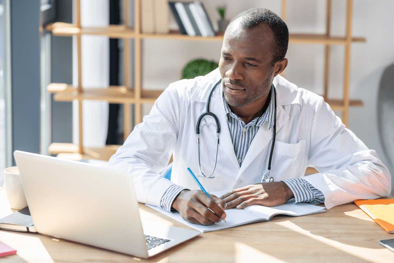 Black-doctor-looking-at-computer-while-sitting-at-workplacjpg