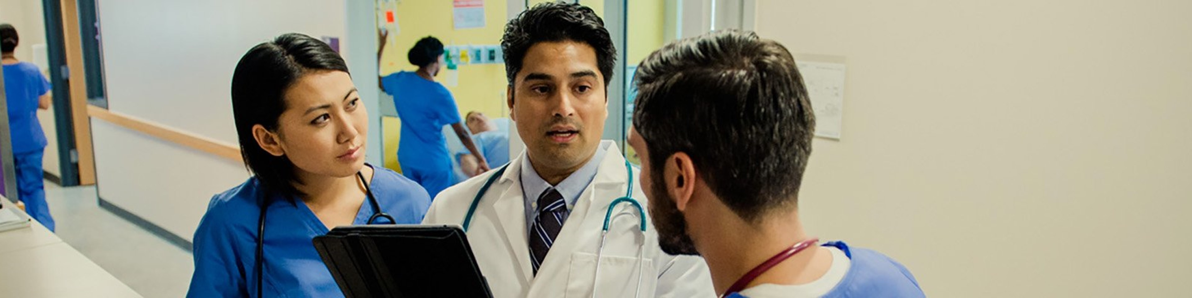 Doctor speaking with staff in hospital hallway