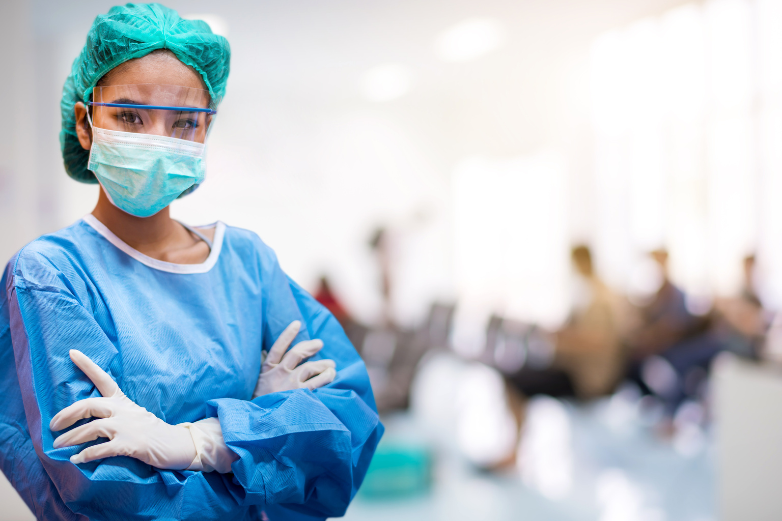 Confident medical professional woman in scrubs and COVID-19 mask
