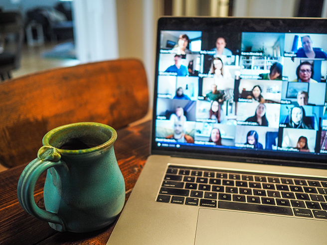 Zoom call on a laptop with coffee mug next to it on table