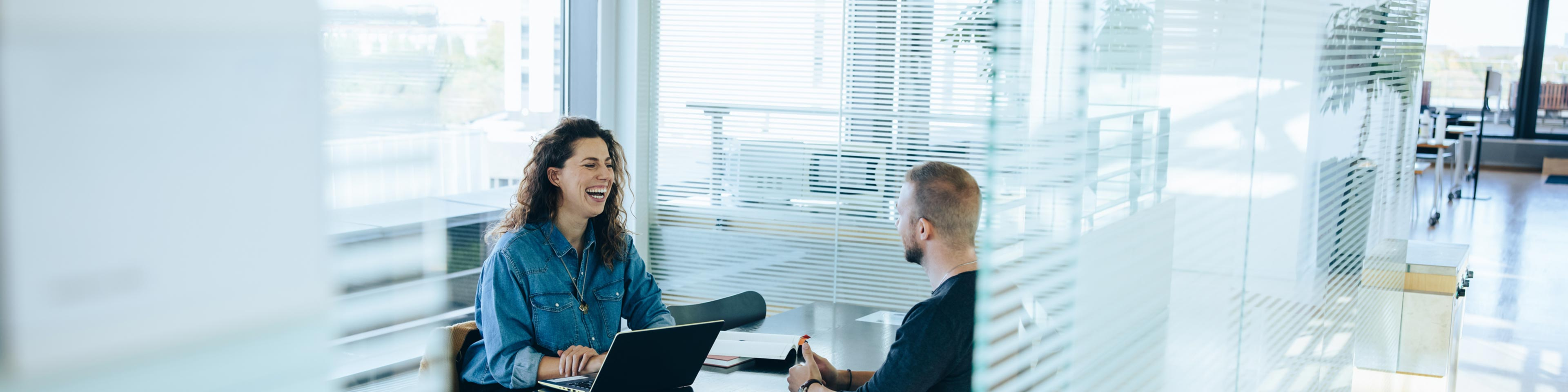 a businesswoman laughing while interviewing a potential candidate in an office setting