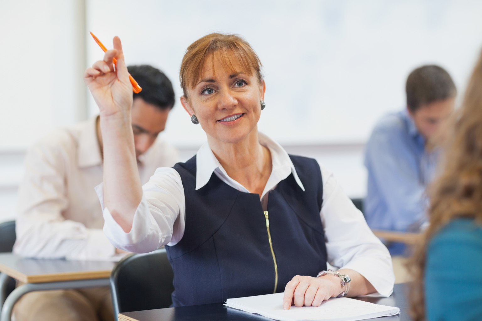 Middle-aged woman sitting in class with hand raised
