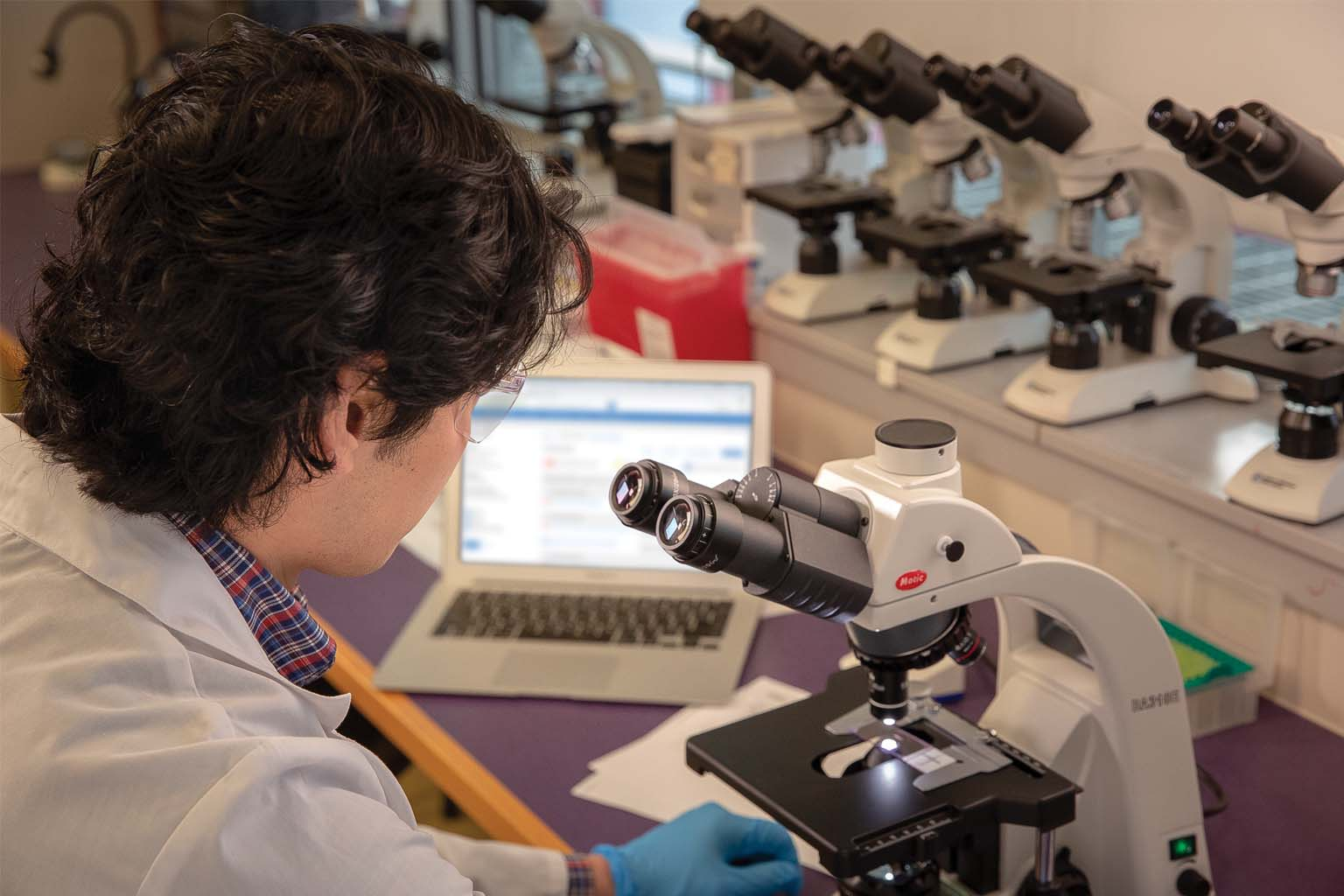 technician in lab with microscope and laptop
