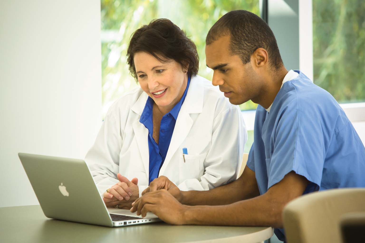 doctor and nurse discussing information on laptop