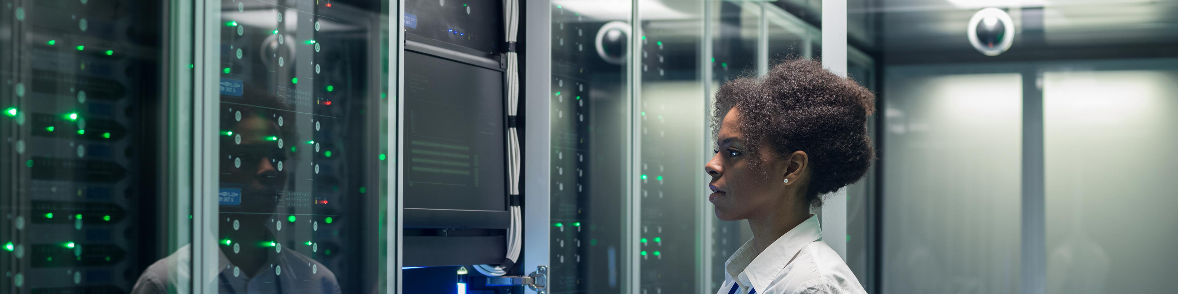 a female employee in a data center holding a tablet and inspecting servers