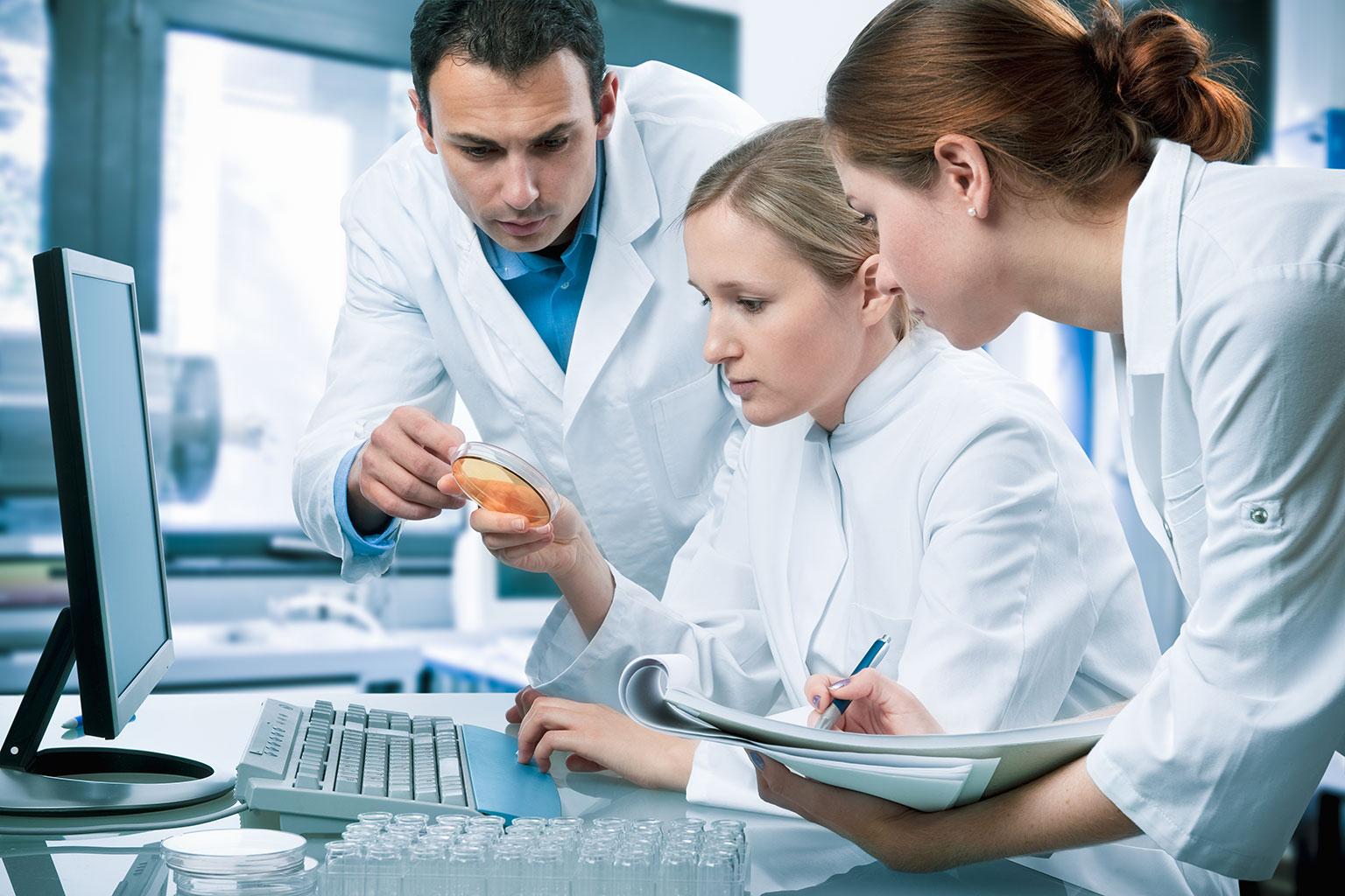 Researchers gathered around a petri dish and monitor