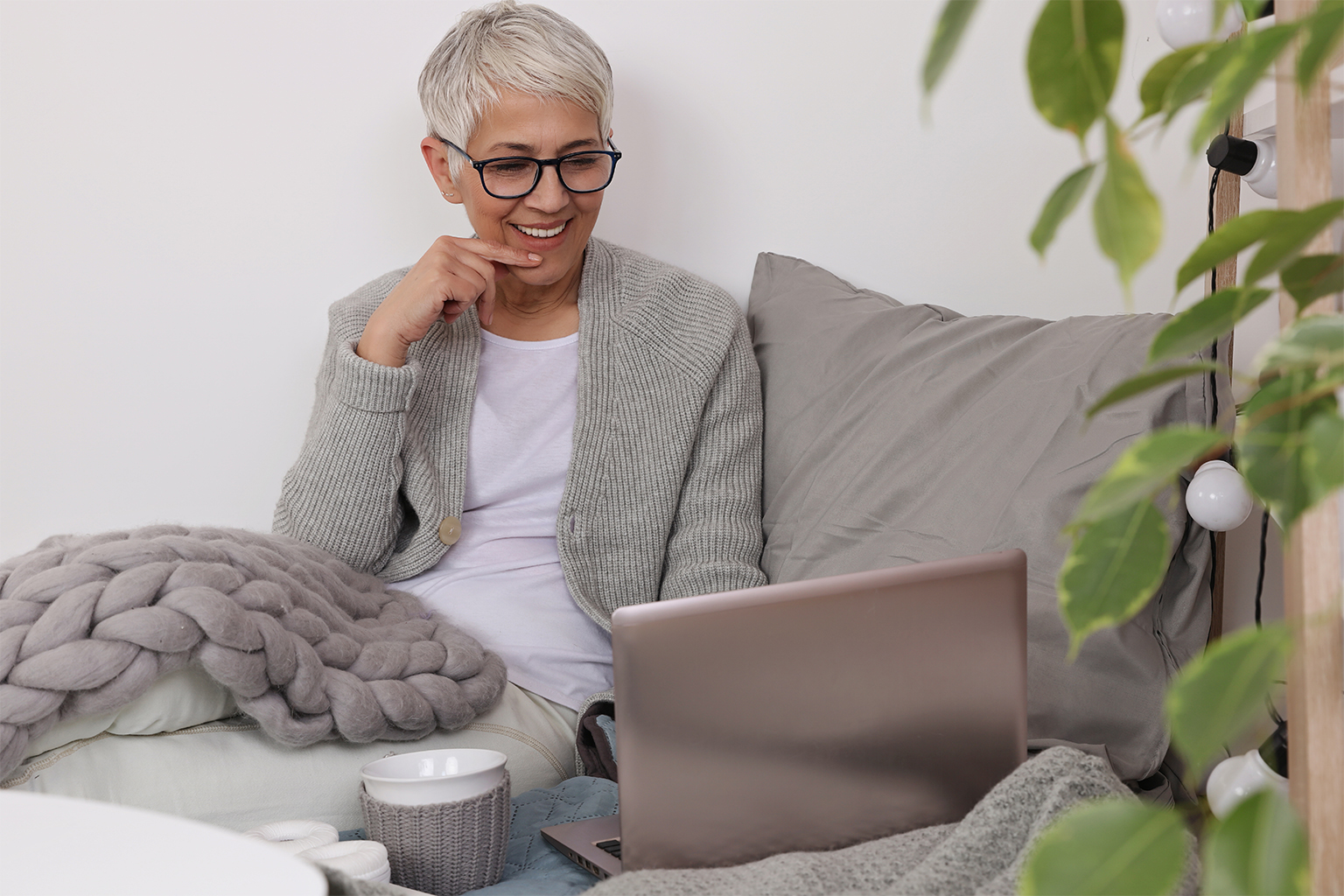 Older woman lounging comfortably with blanket and mug, working at laptop