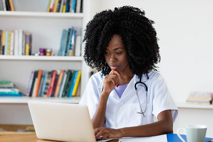 Nurse sitting at desk working on laptop