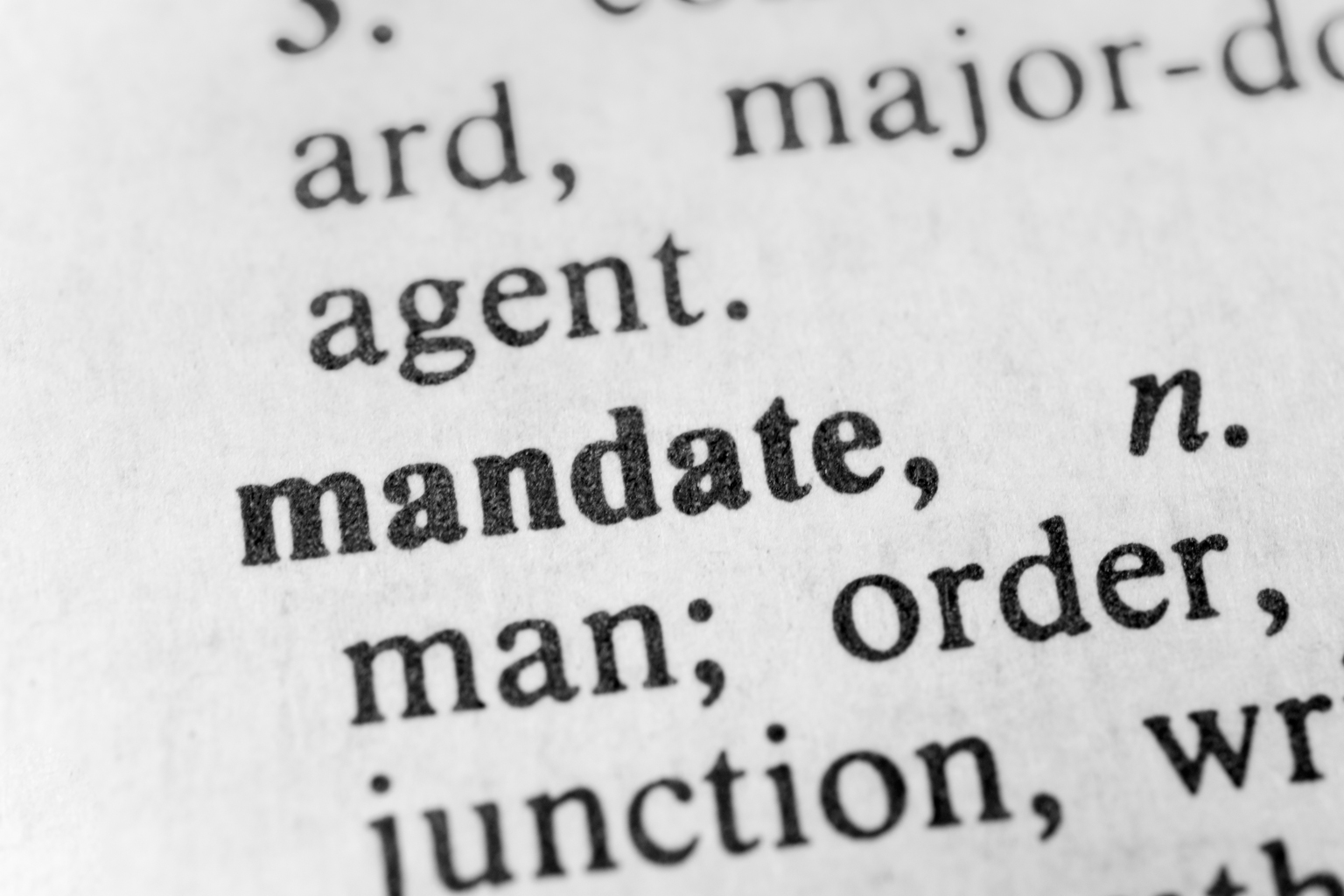 Close up of the word mandate in a dictionary