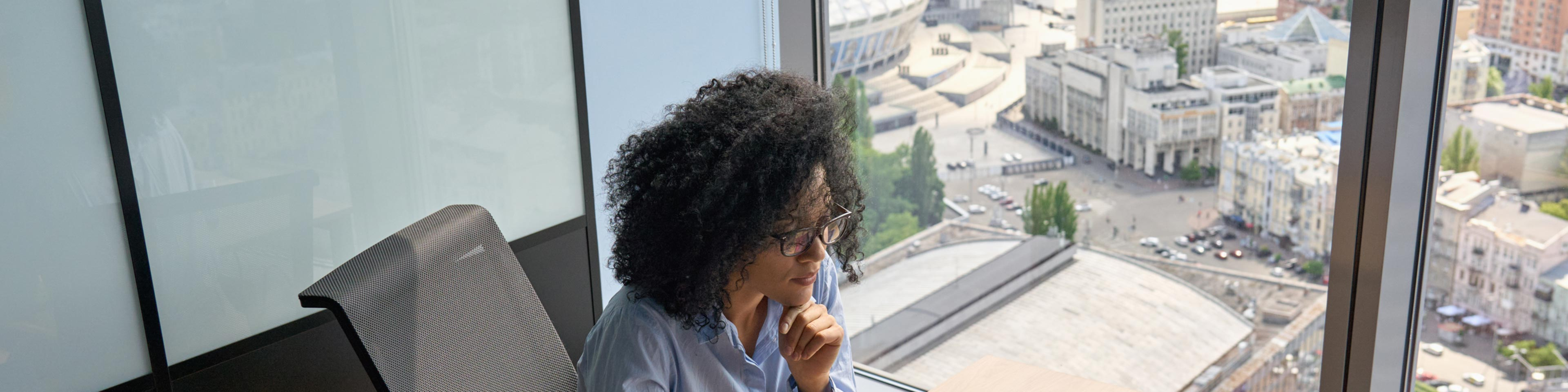 girl sitting at her desk by a window with a view of the city