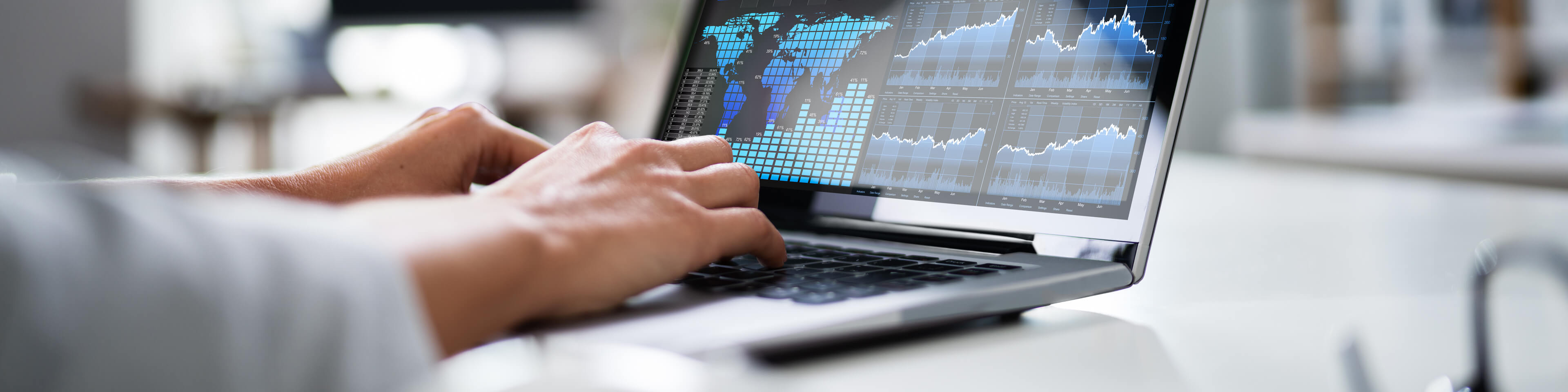 laptop screen showing charts and a world map in data, person typing on the keyboard