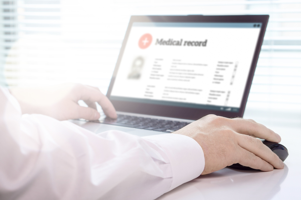 Close up on person's arms on laptop and mouse with medical record page open on the screen