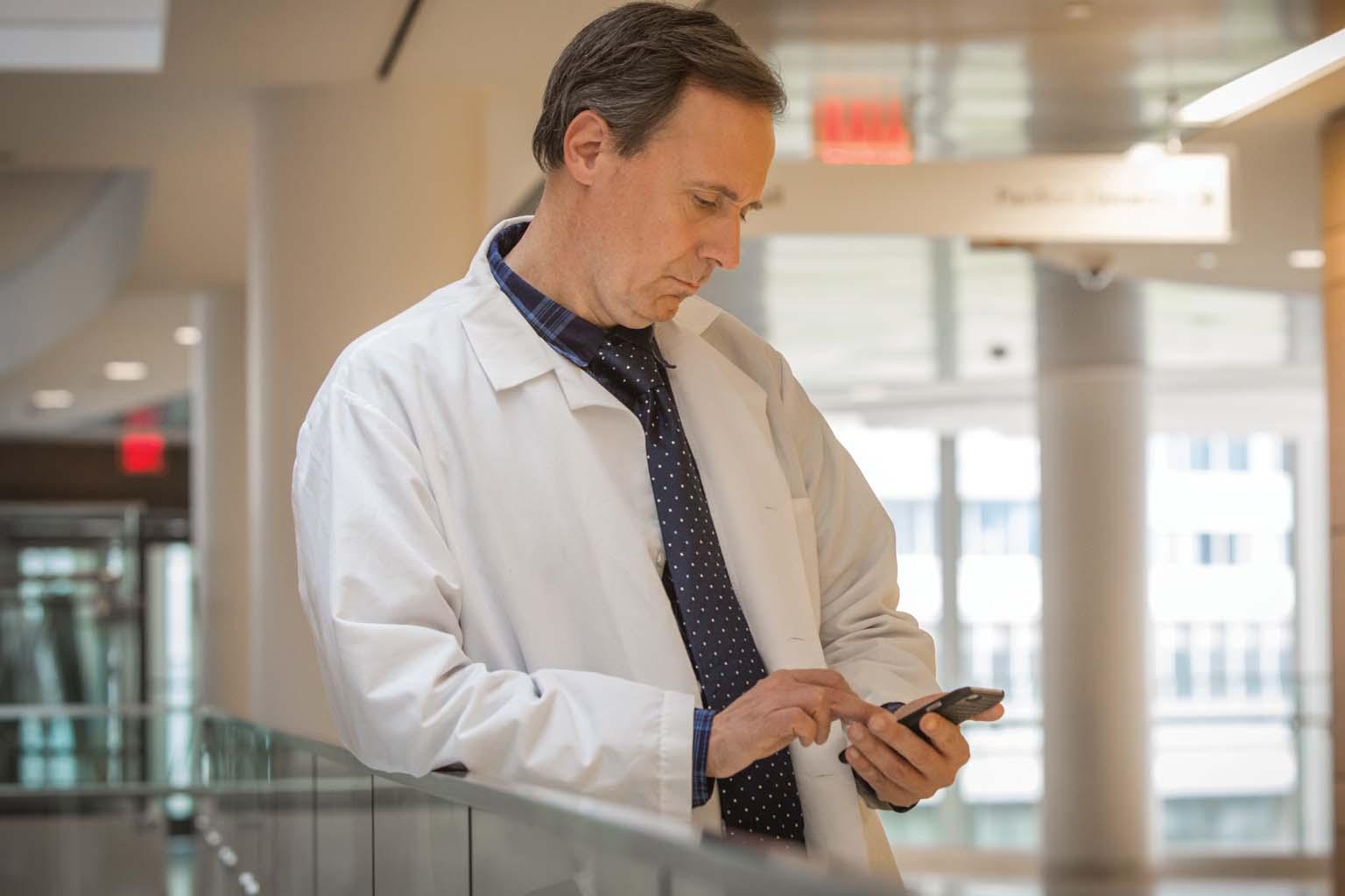doctor paused in hallway looking at smartphone