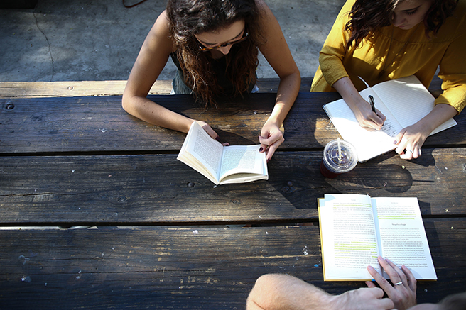 Birdseye view of three people sitting at picnic table studying