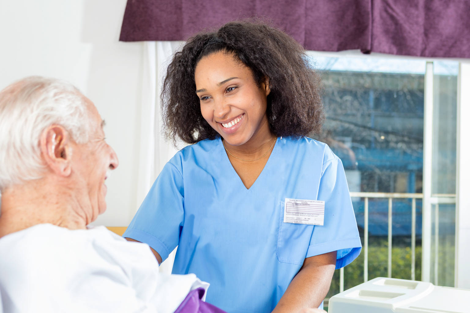 Nurse smiling at patient laying in hospital bed