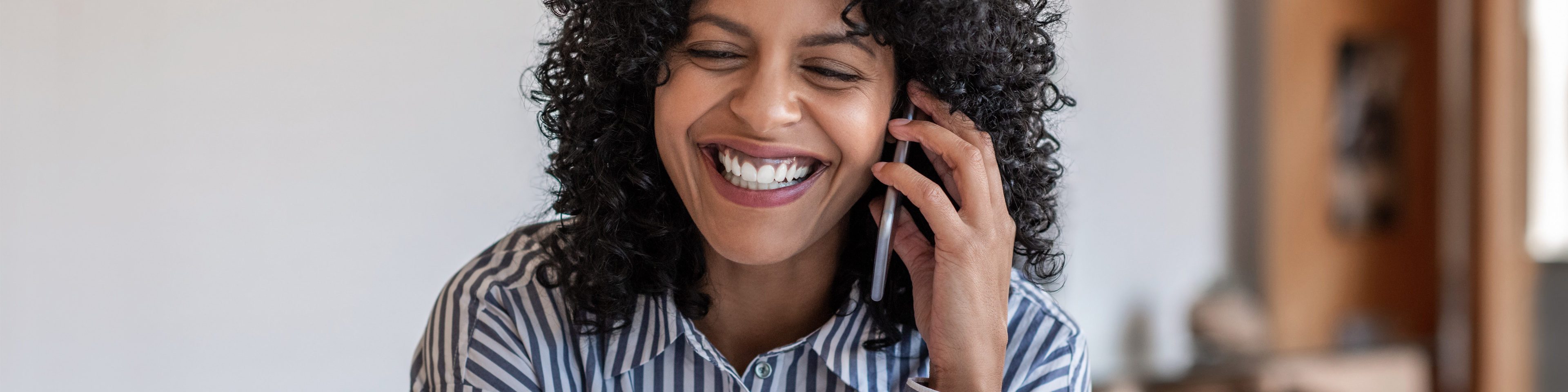 Laughing female entrepreneur talking with a client on cellphone