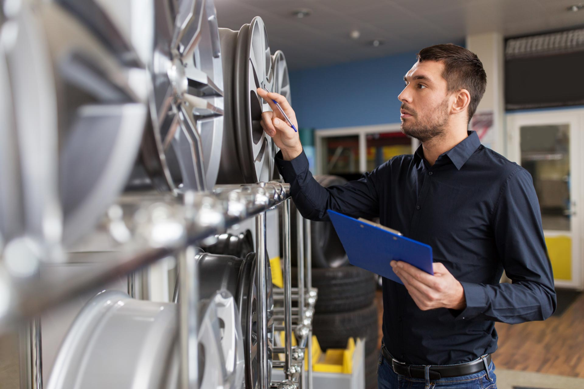 Employee of an S corporation taking stock of car rims