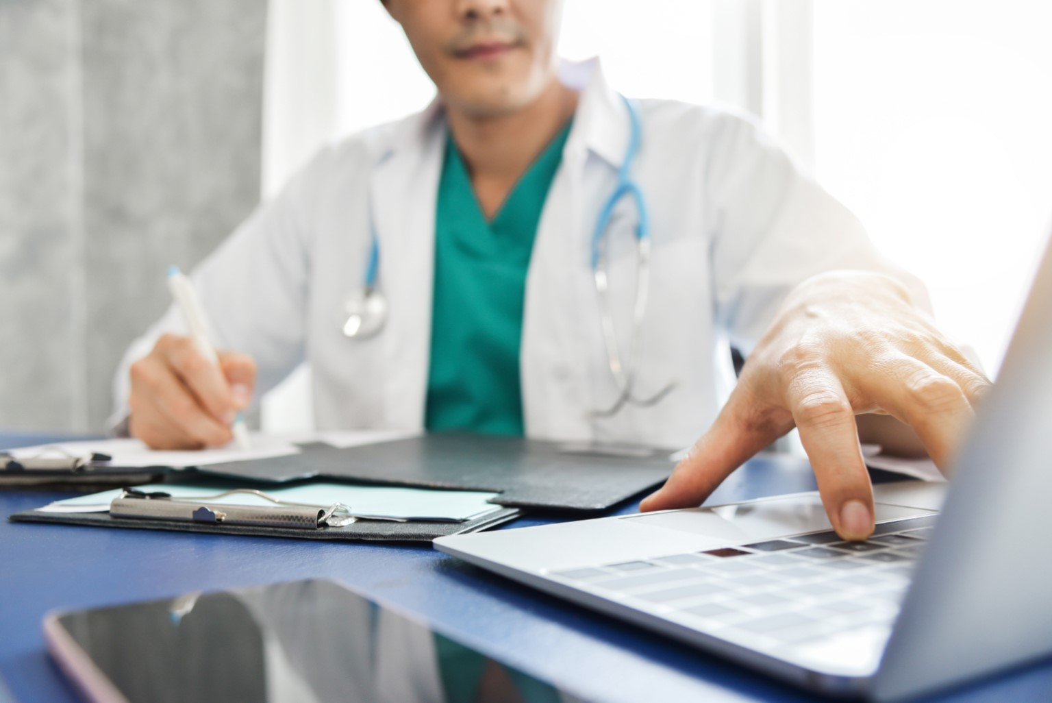 Young-Asian-male-Doctor-thinking-and-working-with-laptop-at-a-hospital-Medical-and-health-care-conce