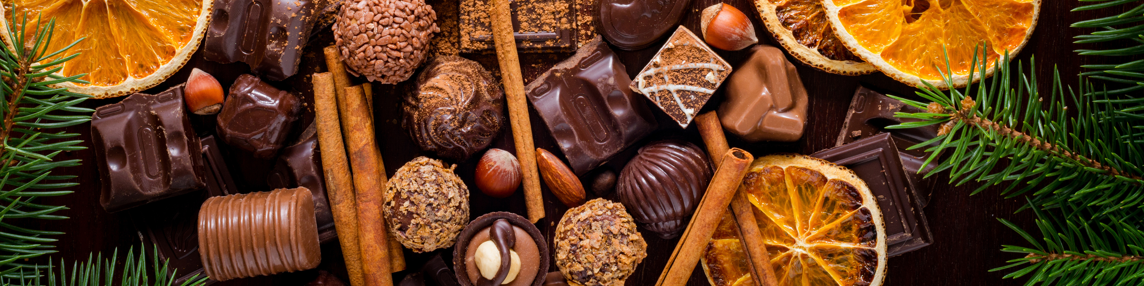 Christmas sweets, chocolates, spices, chocolate truffles and dried oranges on wooden background