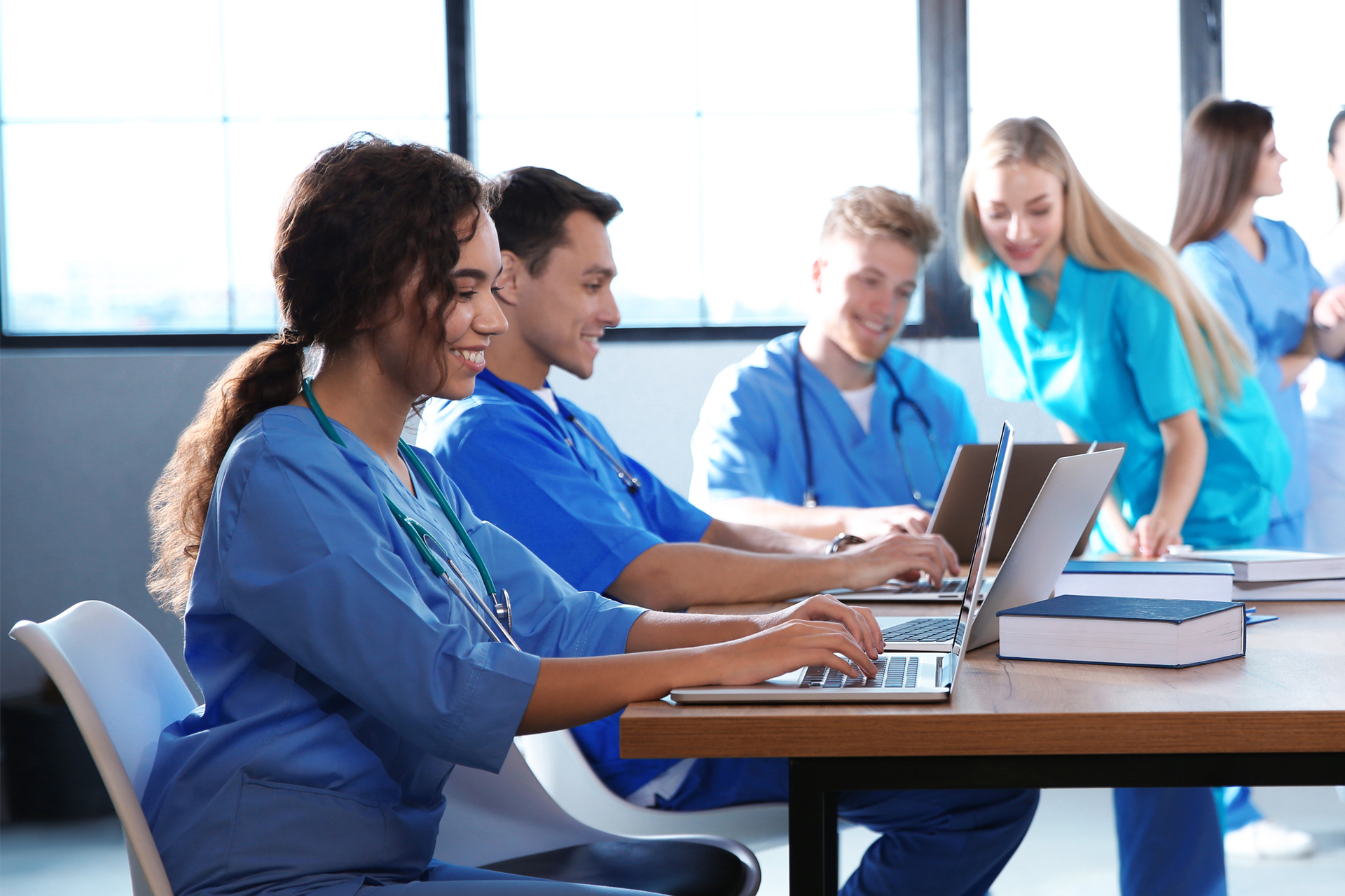 Group of nurses working at laptops in conference room