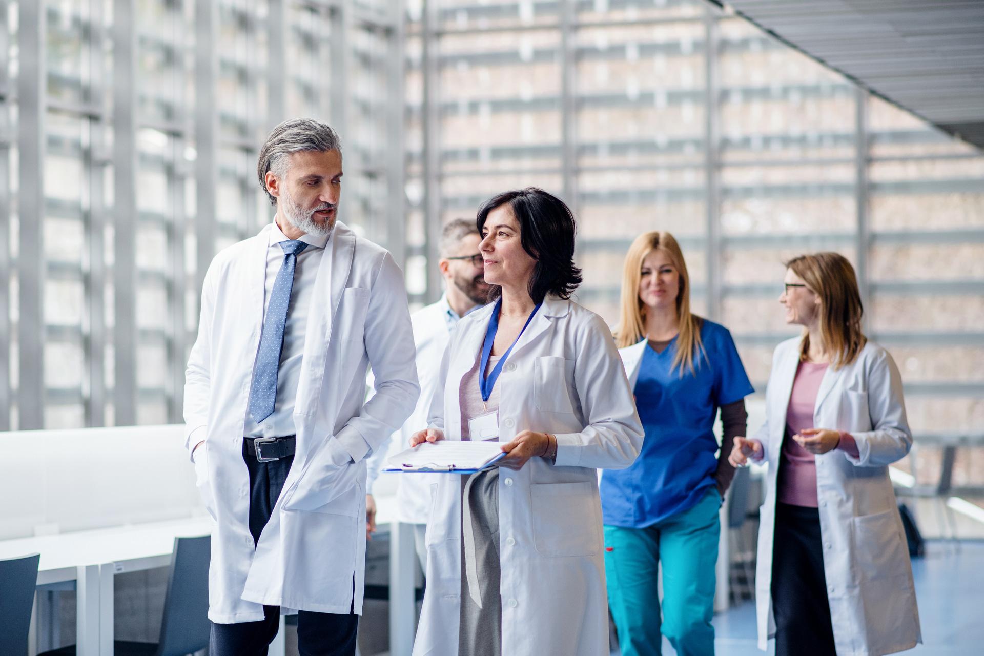 Grupa lekarzy idzie korytarzem w szpitalu, który ma LEX Compliance Medica