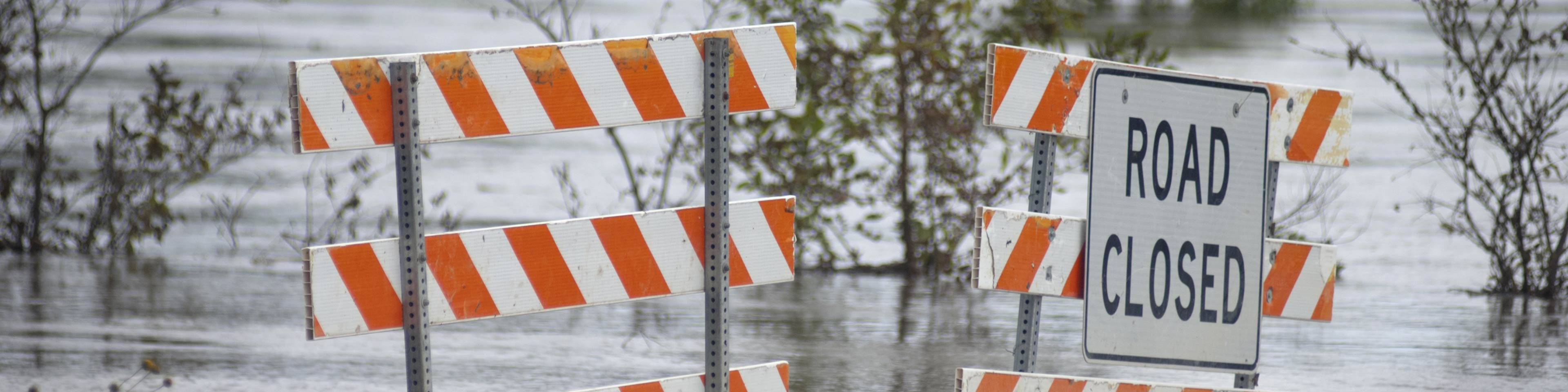 Flooded road with a sign that says Road Closed