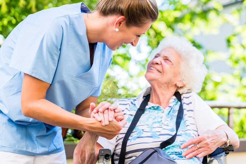 Nurse leaning down to and holding hand of older woman sitting in chair