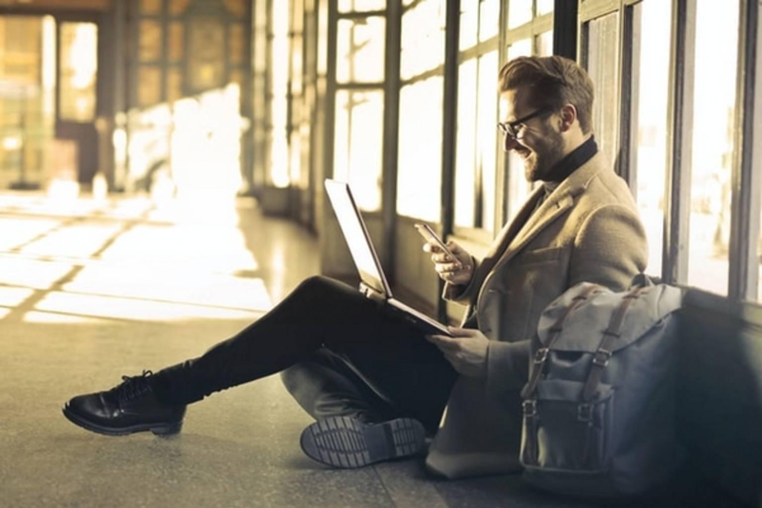 Man on laptop sat on floor