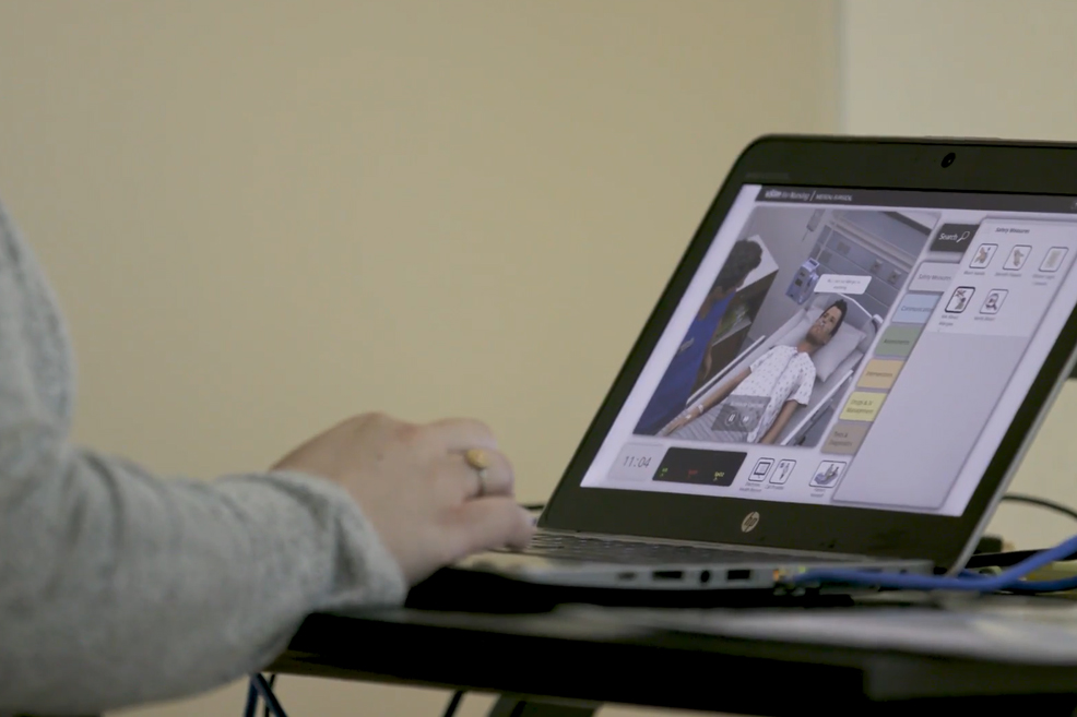 View of vSim for Nursing on a laptop, seen from over the shoulder