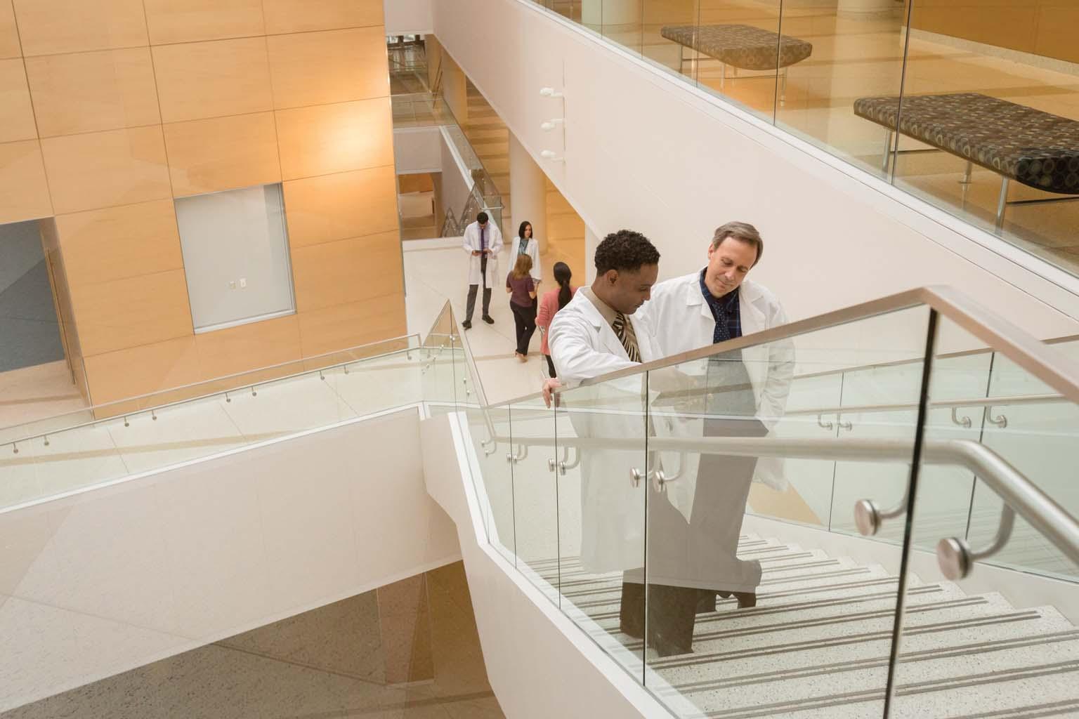 two doctors talking on stairway landing