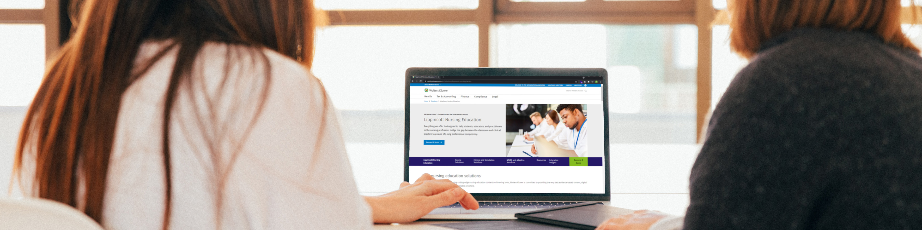 Two women looking at Lippincott Nursing Education website on a laptop screen, their backs to the camera