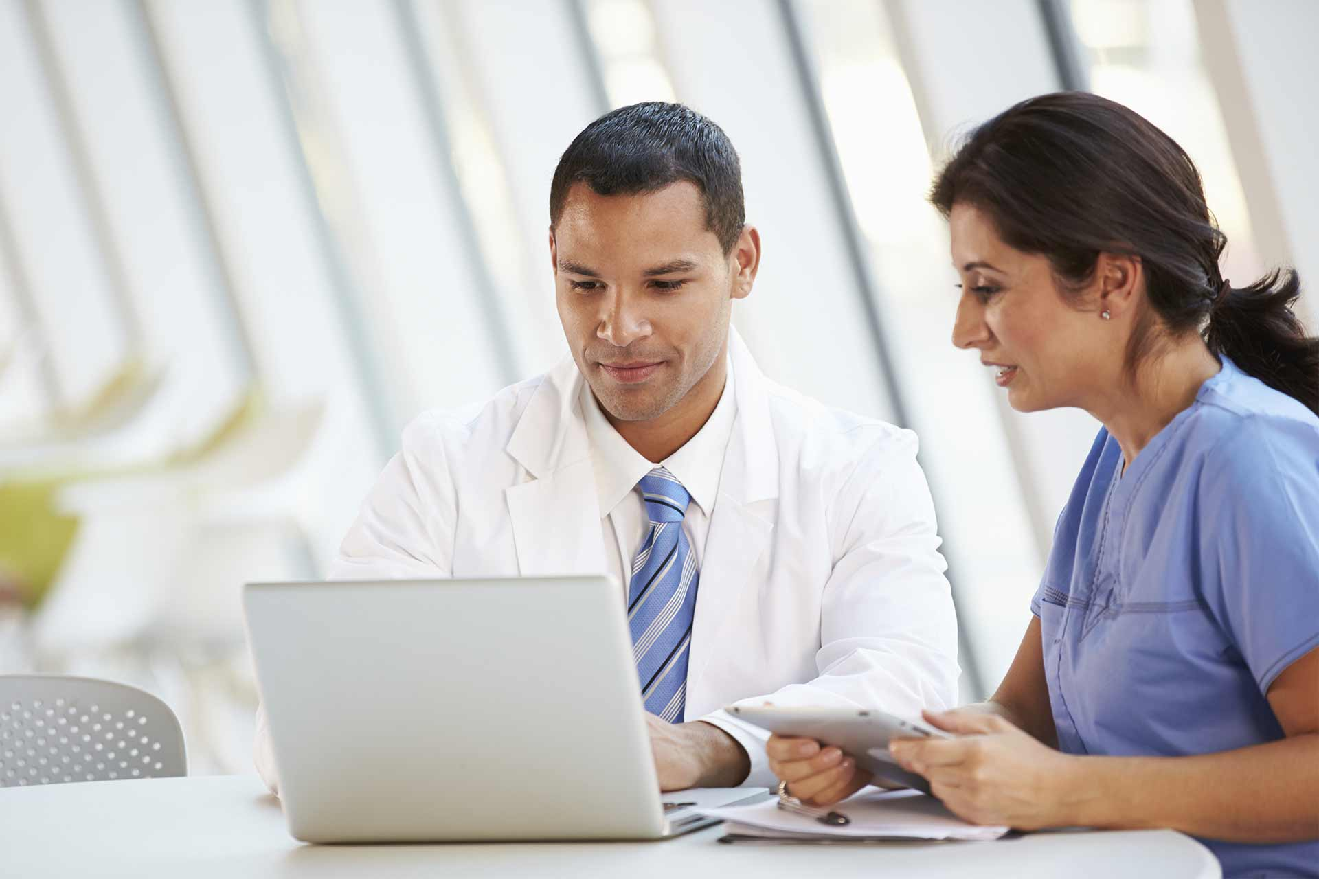 clinician-reviewing-laptop-in-hospitals