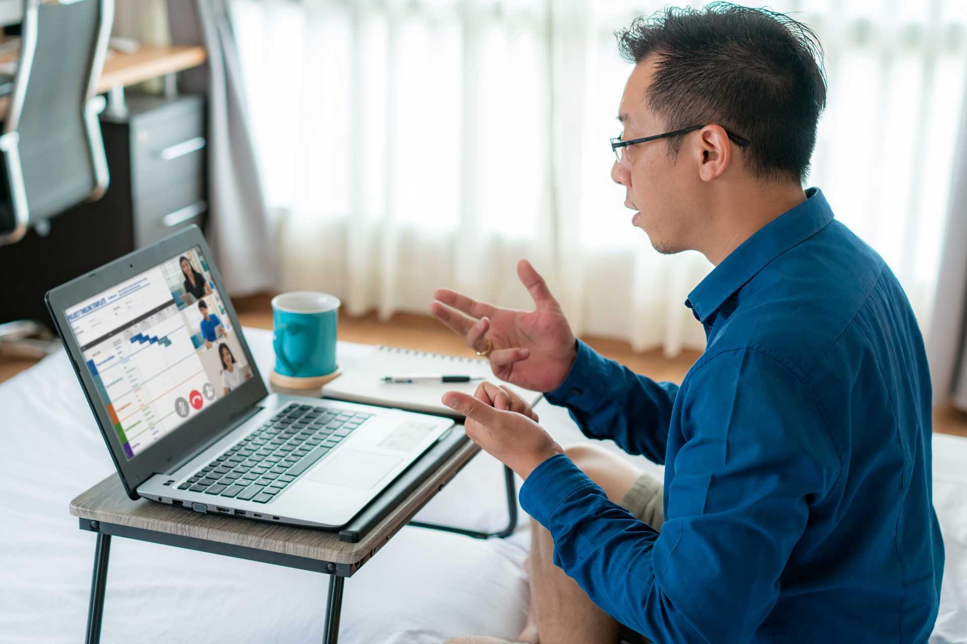 Man videoconferencing on hotel bed