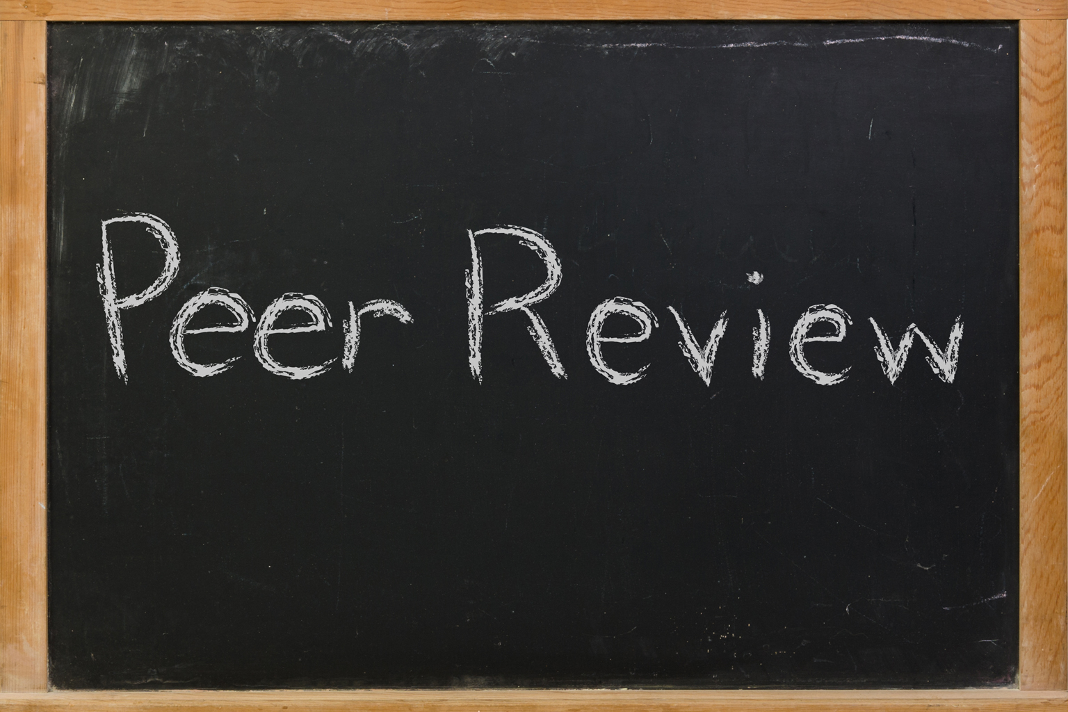 Peer review written on a chalkboard