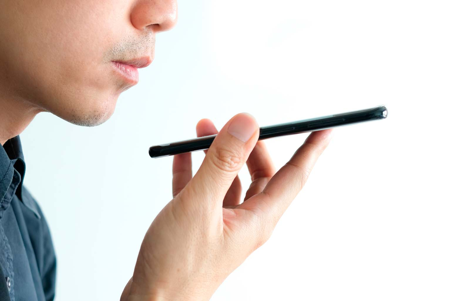 closeup of individual using voice recognition on smartphone