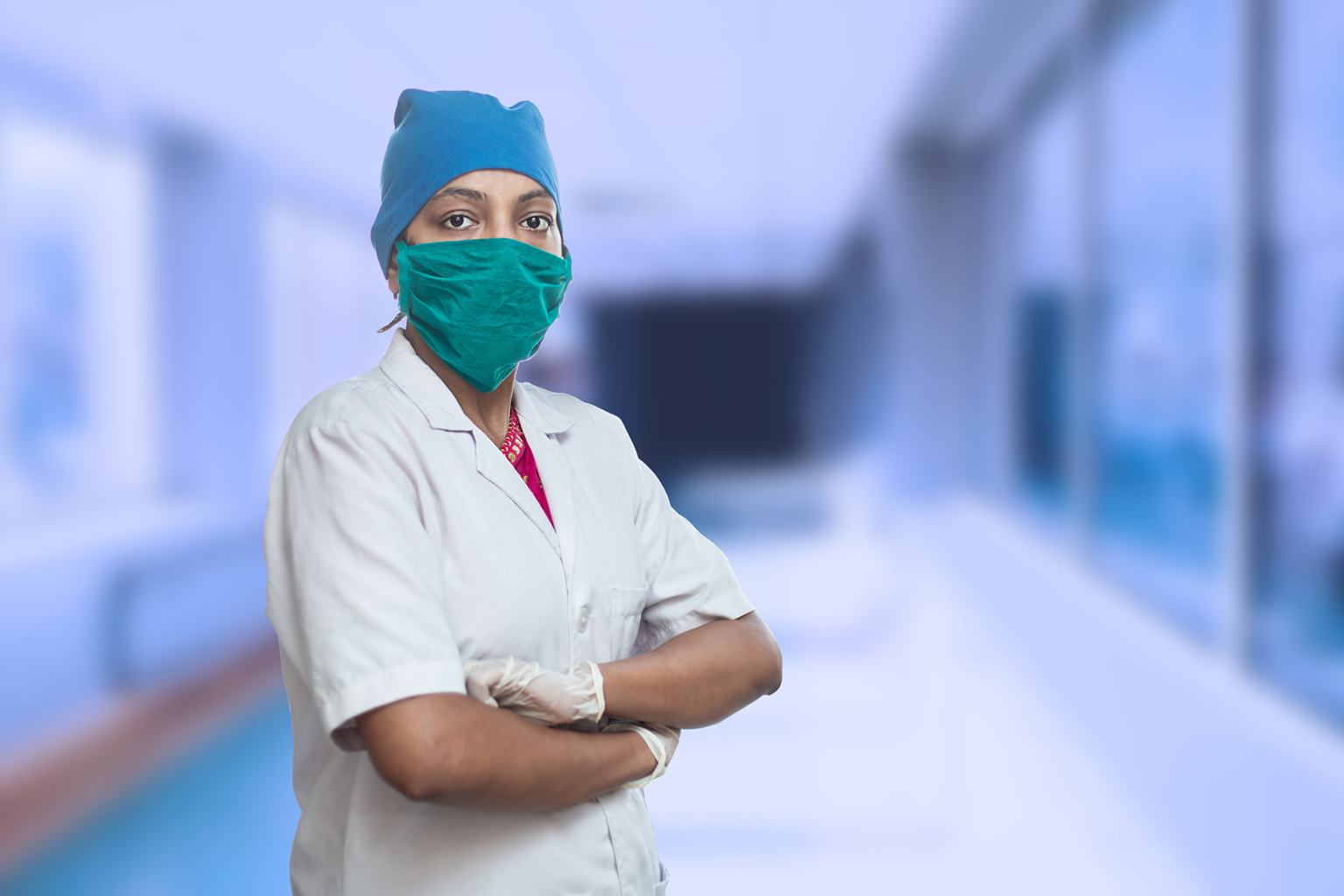 Portrait of female medical worker doctor wearing surgical mask and cap standing crossed arms outside hospital corridor covid-19 coronavirus pandemic