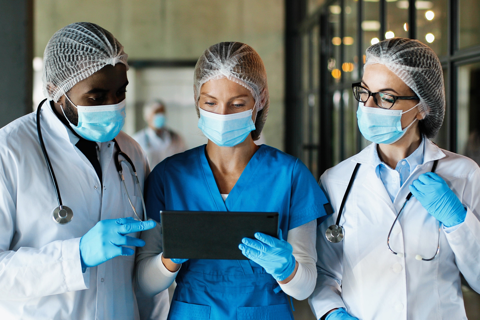 Mixed races male and females healthcare workers in hats medical masks and gloves walking in hospital and talking using tablet device