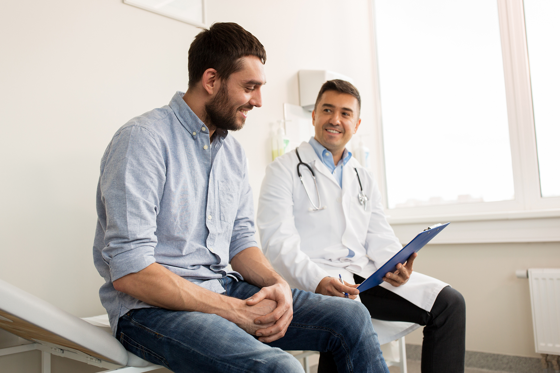 Doctor sitting with patient showing them something in a folder