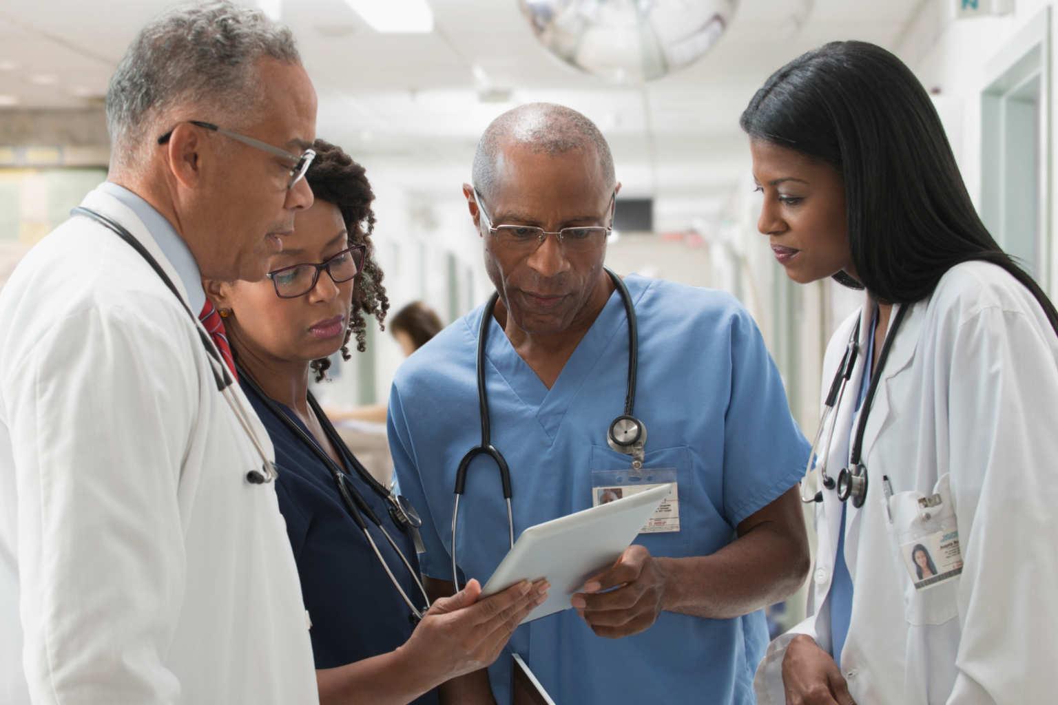doctors huddle over tablet