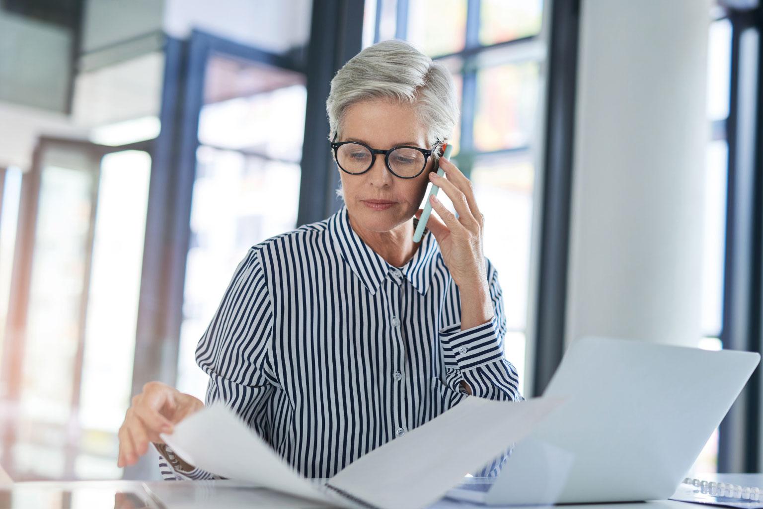 Pracownica szpitali przegląda dokumenty, telefonuje i na komputerze ma LEX Medica