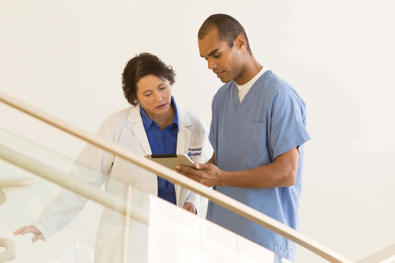 doctor and nurse looking at tablet on stairway