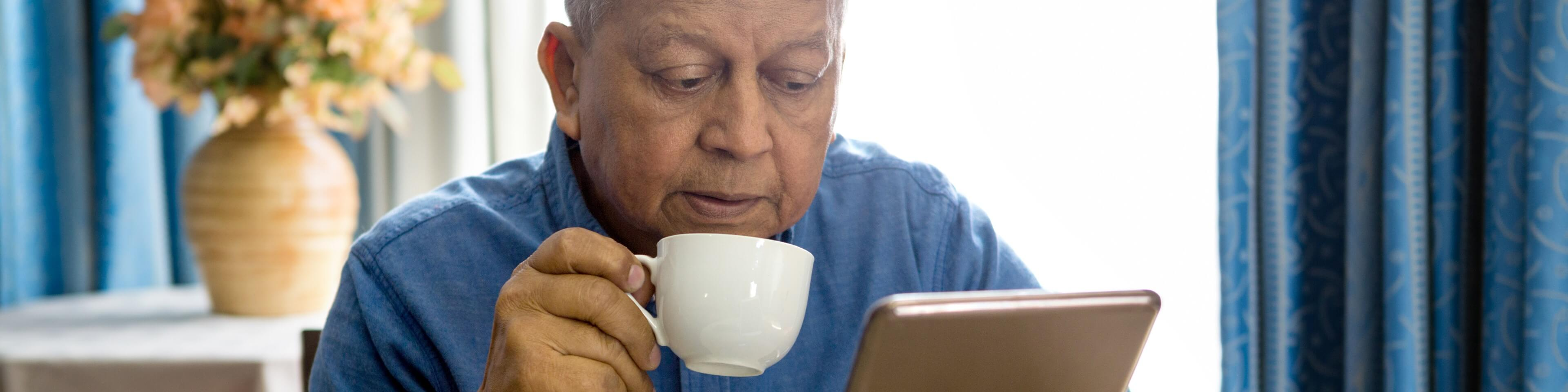 Patient drinking coffee while browsing with a tablet