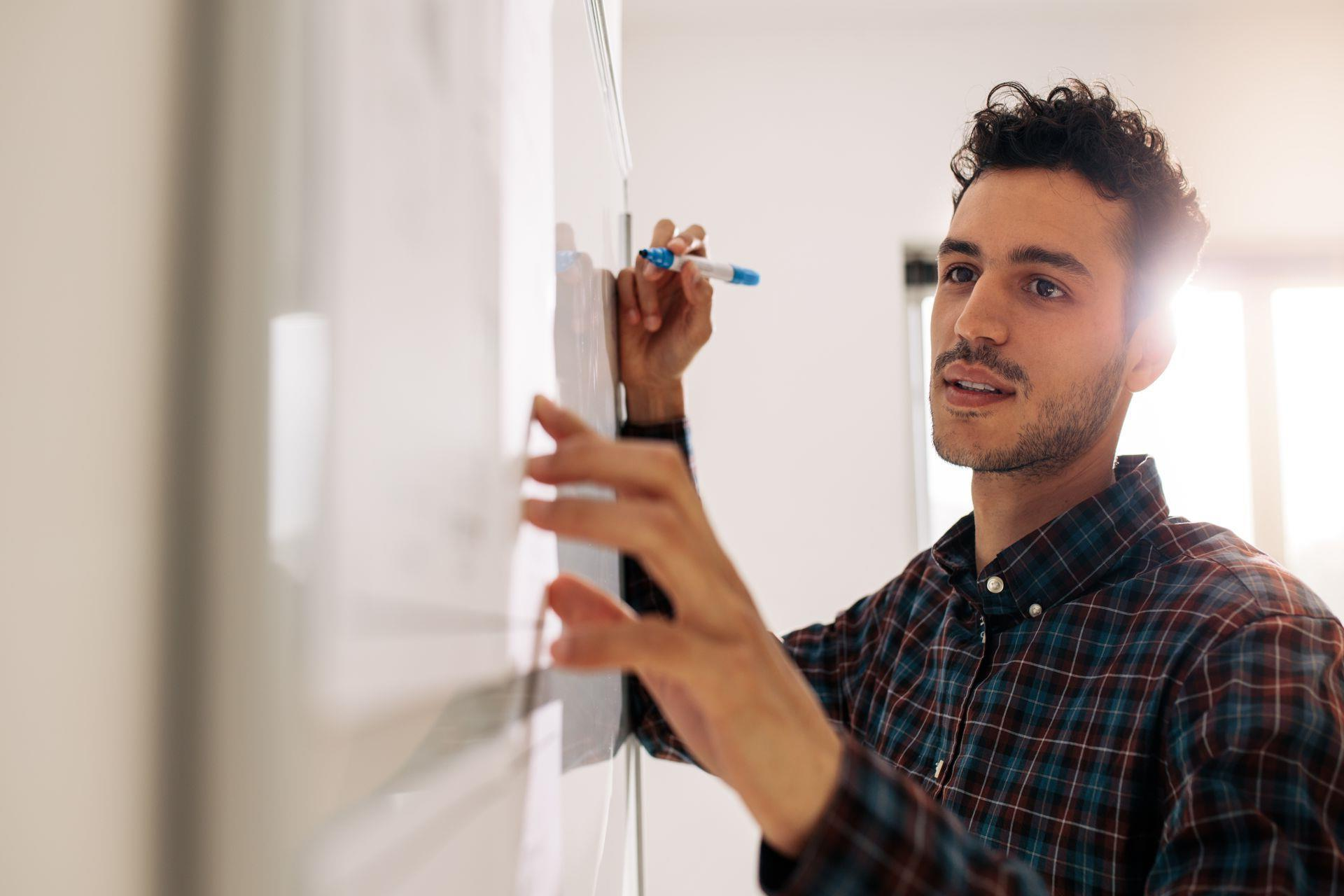 man with whiteboard making a plan to launch his business