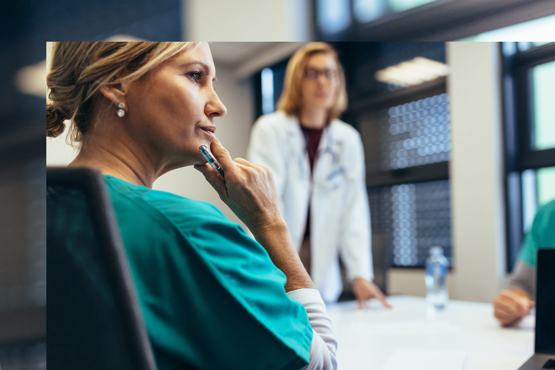 Focus on nurse sitting at meeting room table with doctor standing, leaning on table in background