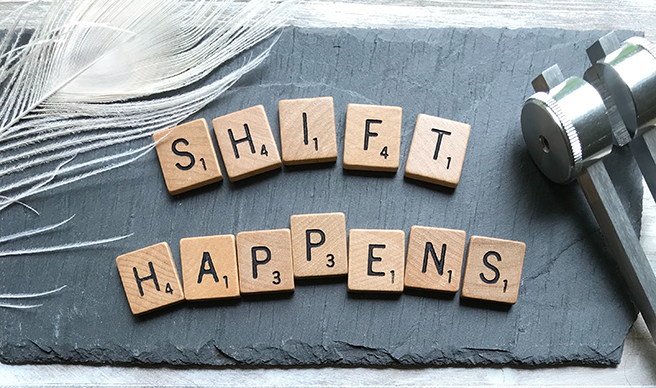 Slate board with the words shift happens spelled out in Scrabble letters