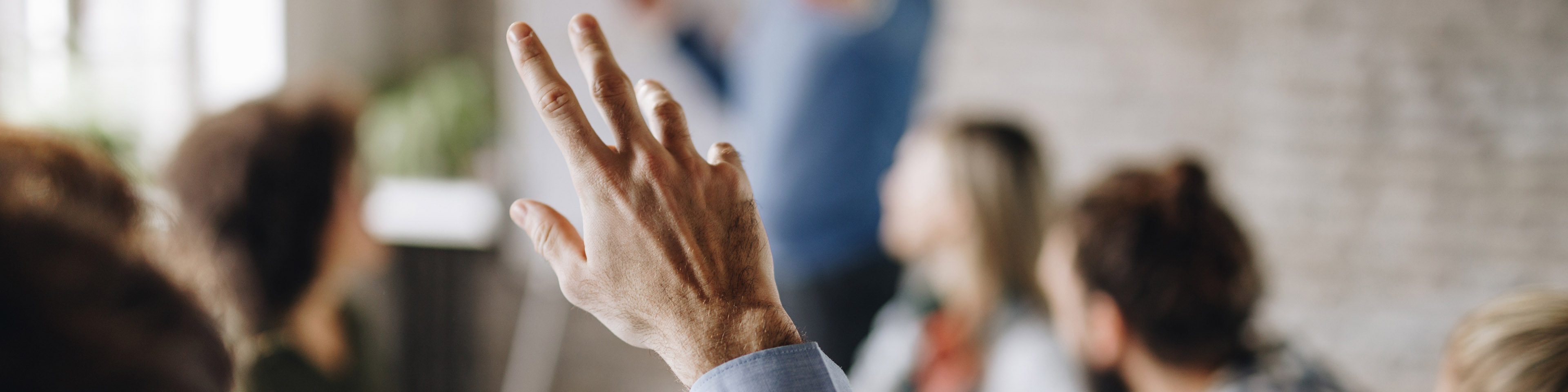 Unrecognizable person raising his hand to ask a question on a business meeting in the office.