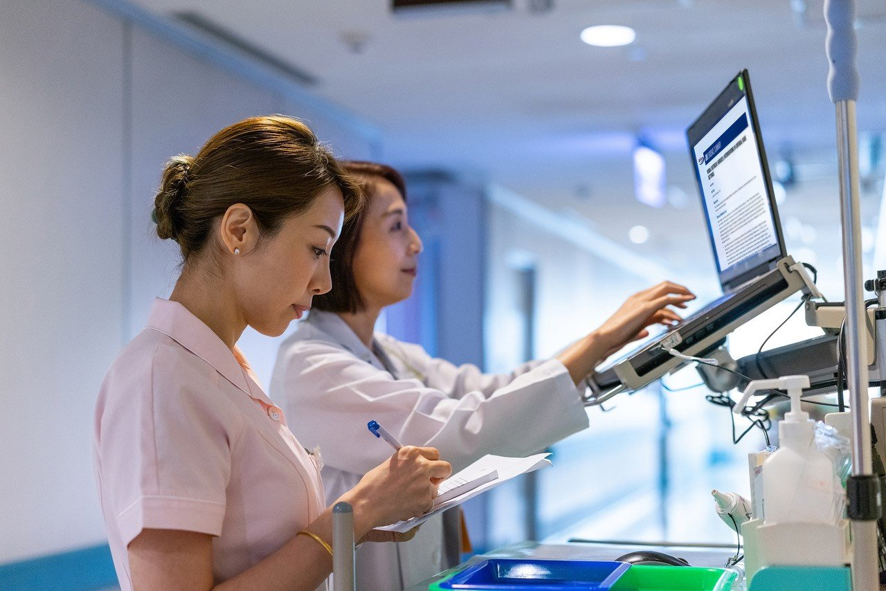 Two female Asian medical professionals working at a laptop station
