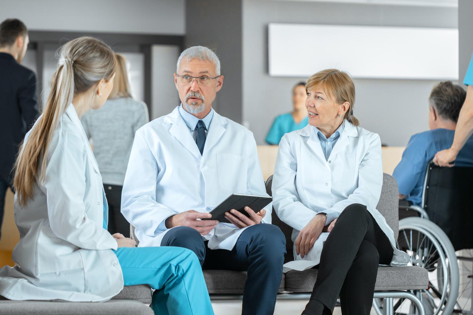 Grupa lekarzy siedzi na ławce w szpitalu rozmawiając o zarządzaniu ryzykiem w Progmedica