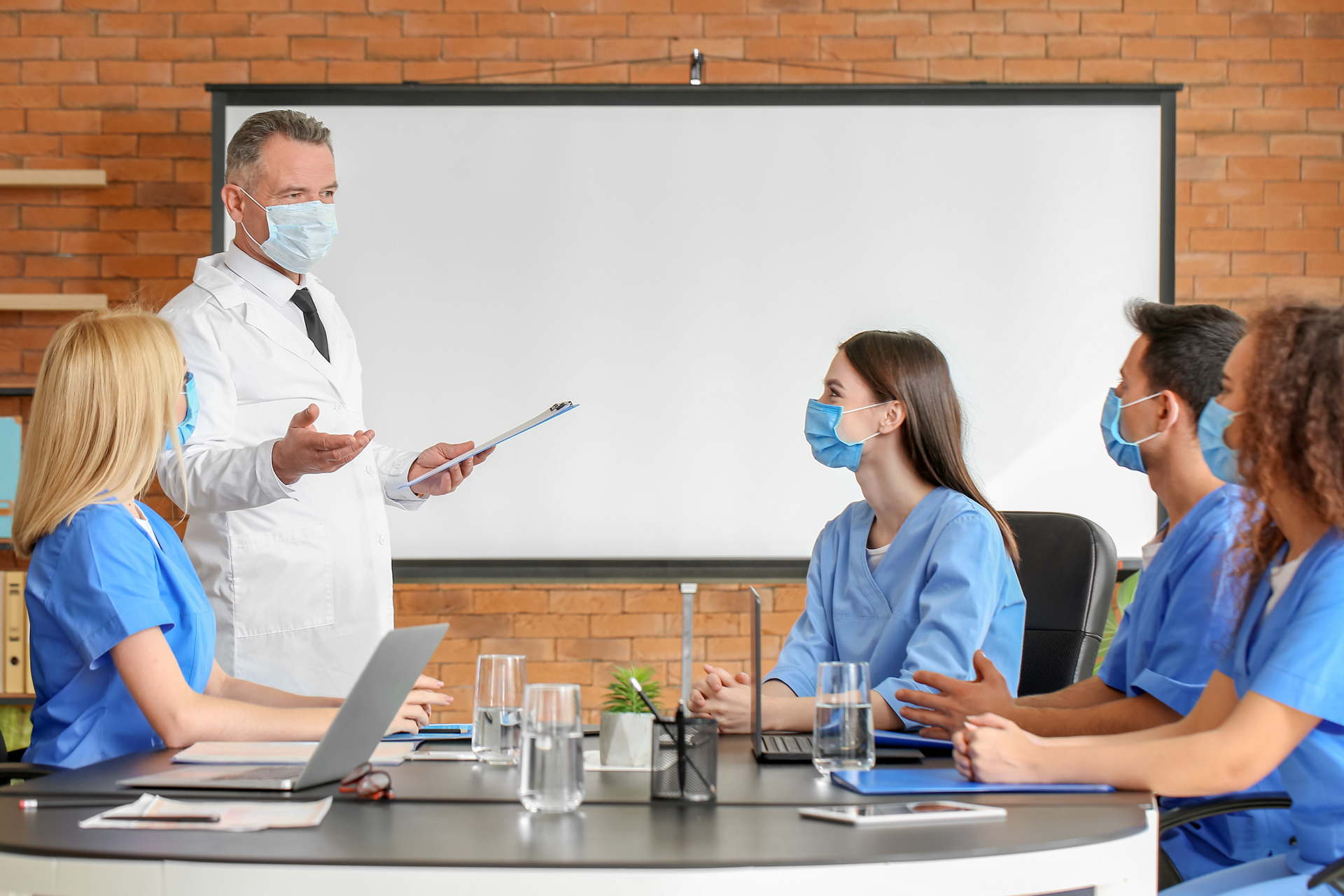 Medical educator and healthcare worker students in classroom wearing face masks
